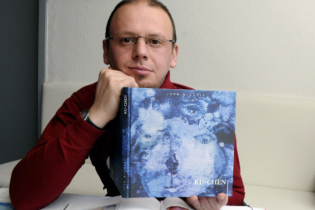"""Jörn Michael - hier mit einem Katalog des Kunstkellers Annaberg - beteiligt sich an der Aktion von """"Leser helfen""""."""