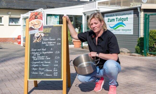 Inhaberin Yvette Mettendorf mit leerem Topf vor ihrer Gaststätte. Hier gibt es derzeit ein Imbissangebot und Eis zum Mitnehmen.