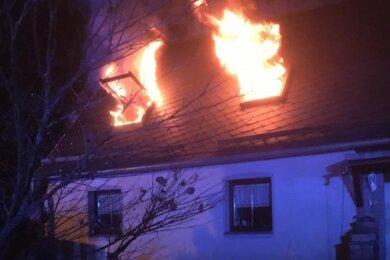 Meterhoch schlugen die Flammen aus den Dachgeschossfenstern eines Doppelhauses an der Maxim-Gorki-Straße. Die Feuerwehr konnte das Übergreifen des Feuers auf die benachbarte Gebäudehälfte verhindern.