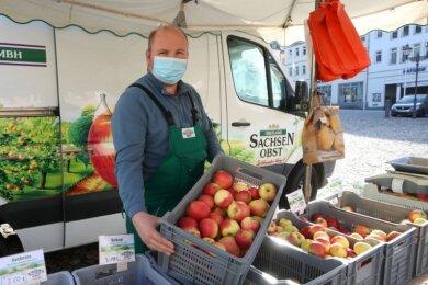 Der Mund-Nasen-Schutz gehört mittlerweile auch auf den Wochenmärkten im Landkreis Zwickau zur Pflicht - wie hier bei Ronald Wenzel, der auf dem Marktplatz in Glauchau Äpfel und anderes Obst anbietet.