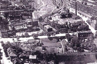 Dieses Luftbild zeigt halbrechts den Bahnhofschacht (mit Schornstein). Vorn verläuft die Kohlenstraße (heute Am Bahnhof), und links steht die Firma Friemann & Wolf (Grubenlampen). Das Gleis (vorn) ist das Personenzuggleis des alten Bahnhofs.