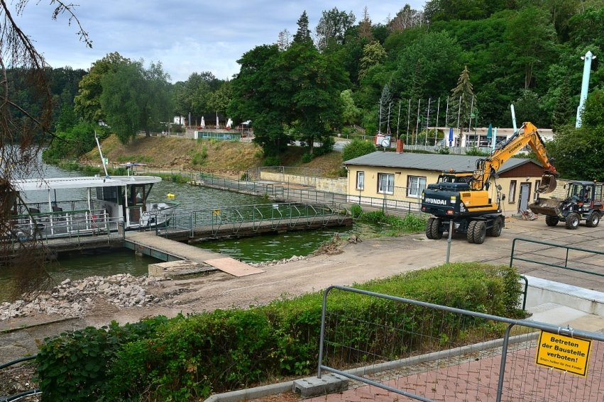 Blick auf den Hafen der Talsperre Kriebstein in Richtung Besucherzentrum: Auf der Schotterfläche (vorn links) soll der Riesenkran aufgebaut werden. Links neben dem Infopunkt (gelbes Haus) entsteht das Gebäude mit Aufzug.