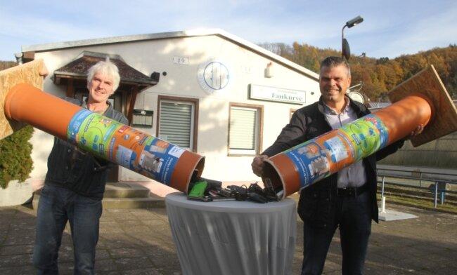 Torsten Rustler (links) vom Nabu-Regionalverband Elstertal und der Gewerbevereinsvorsitzende Sven Haller entleeren die Sammelbehälter mit den alten Handys. Diese sollen nun der Rohstoffgewinnung zugeführt werden. Die Erlöse fließen in den Insektenschutz.