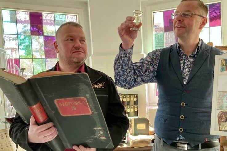 Während Lautergold-Betriebsleiter Mike Schneising im Rezeptbuch stöbert, legt Schneebergs Bürgermeister Ingo Seifert einen prüfenden Blick auf den traditionellen Weißbitter aus der Bergstadt.