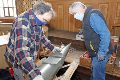 Orgelbauer Andreas Hahn (l.) und Domküster Otto Schröder begutachten die ausgebaute Orgelpfeife.