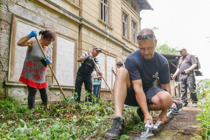 Toni Naumann (vorn) und Helfer aus Wolkenburg legen das Gelände am alten Bahnhofsgebäude in Wolkenburg frei.