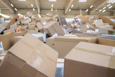Pakete liegen in einem Paketzentrum von DHL. Wer bekommt was vom Porto ab?