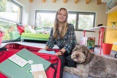 Lea Stütz vor der Abreise beim Packen mit Hund Pico. Als Geschenk hat sie einen Faltstern mitgenommen.