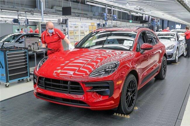 Im Leipziger Porsche-Werk wird die Produktion eines vollelektrischen Macan vorbereitet. Noch laufen vor allem Fahrzeuge mit Verbrennungsmotor vom Band. Ein Mitarbeiter führt hier mit Mundschutz die finale Qualitätskontrolle an einem Macan durch.