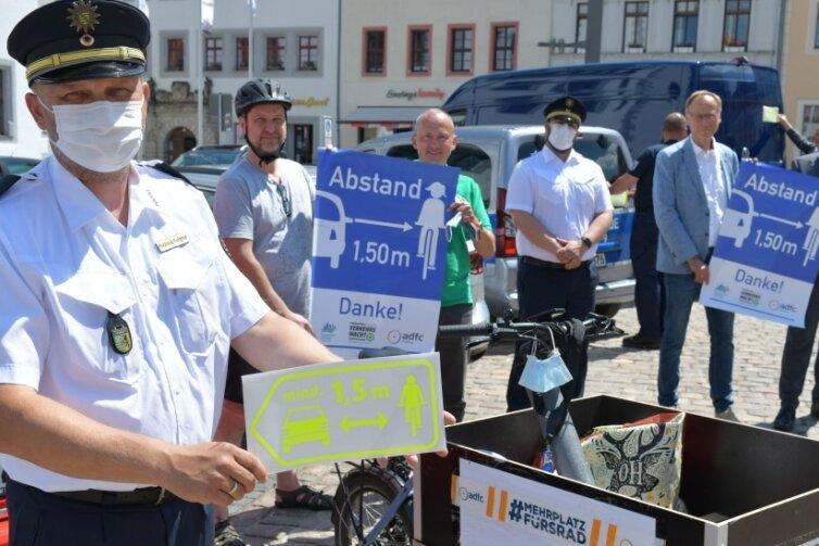 Polizeirat Andreas Felgner (links) unterstützt die gemeinsame Aktion - der Leiter des Polizeireviers Freiberg zeigteinen der Aufkleber, die an den Dienstfahrzeugen der Ordnungshüter angebracht werden. Zugleich kündigte er für den 14. September eine Großkontrolle für Fahrradfahrer in Freiberg an.
