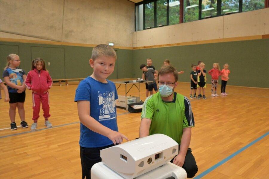 Am Kindersprintnahmen auch die Zweitklässler teil. Markus Albitz vom Expika-Team (vorn rechts) erklärt dem achtjährigen Elias Möbius aus Oelsnitz, wie er den Computer bedient und den Sprint starten kann.