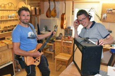 Roy Fankhänel (links) aus Oelsnitz und Tim Walter aus Burgstädt haben die Gitarrenmanufaktur Odem gegründet. Mit dem neuen Teil wird schon mal in der Werkstatt abgerockt.