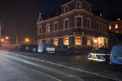 """Polizei vorm Hotel """"Zur Post"""" in Schönheide. Vorausgegangen war eine anonyme Anzeige, weil es jemandem verdächtig war, dass viele Autos vorm Haus standen und die Fenster der Gaststube hell erleuchtet waren."""