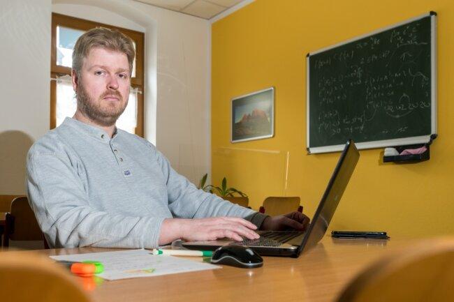 Statt mit Schülern sitzt Denis Kindt allein im Unterrichtsraum, von wo aus er zumindest einigen Schülern via Internet Hilfestellung geben kann.