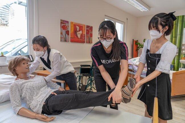 Demonstrieren im Praxiskabinett, dass sie fit sind für die Arbeit in der Pflege: Tuoi Phung (26, von links), Nhung Bui (28) und Oanh Nguyen (23). Die jungen Frauen aus Vietnam haben als erster Jahrgang erfolgreich die Ausbildung zur Pflegefachkraft bei der Awo Vogtland beendet.