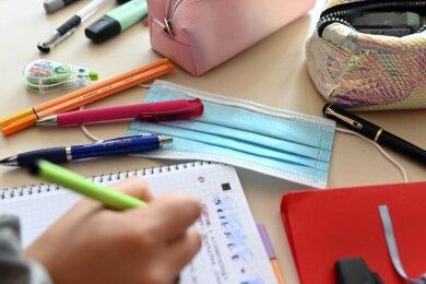 Ein Mund-Nasen-Schutz liegt auf dem Tisch einer Schülerin.
