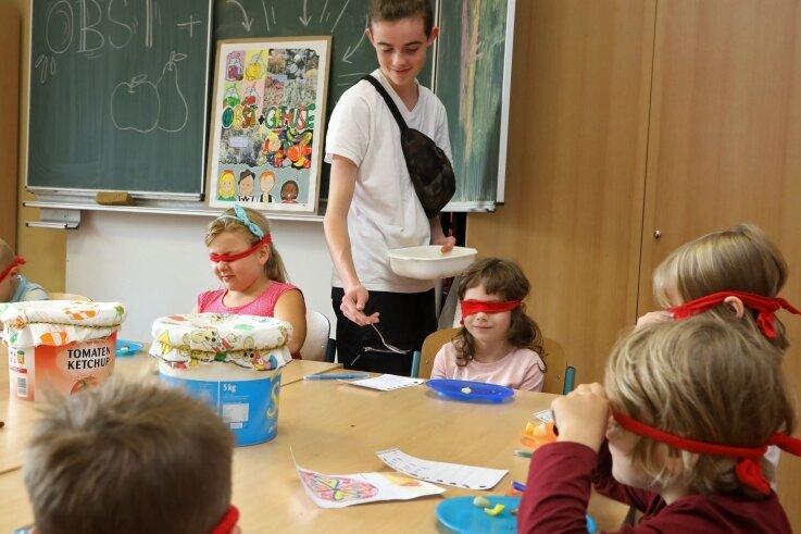 Der Freiwilligendienstleistende Antony Peger verteilt an Kinder der Grundschule in Langenberg bei einem Projekt Früchte. Mit verbundenen Augen sollen diese gekostet und so erkannt werden.