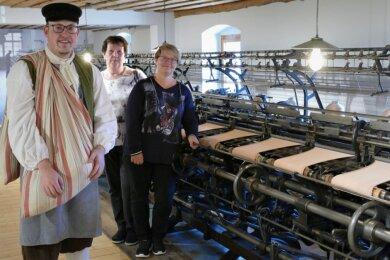 Robby Schubert als Quersackindianer, Susann Hofmann und Ingrid Werner (v. l.) wollen im neu gestalteten Gelenauer Strumpfmuseum altbekannte Thematik mit frischem Pep vermitteln. Trotz neuer Ideen gehört die 90 Jahre alte Cotton-Maschine, an dem das Trio hier steht, weiterhin zu den Highlights der Ausstellung.