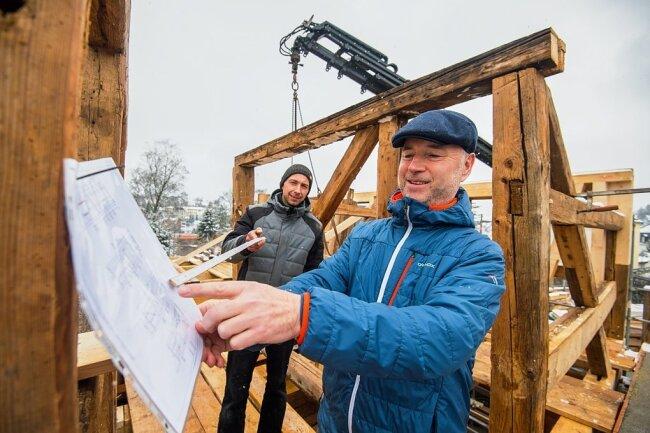 Zimmerermeister Markus Günther (links) zeigt Bauherrn Steffen Seifart, wie nach den Plänen das Gebäude 1:1 in Schneeberg wieder aufgebaut wird.