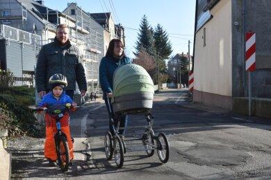 Silvia und Arndt Scholze laufen mit ihren Kindern Philip und Oskar (im Kinderwagen) die Köthensdorfer Hauptstraße entlang. An der Engstelle am Grundstück Nummer 43/44 wird es für sie auf der Straße gefährlich, denn dort fehlt der Fußweg und die Straße ist zu eng für zwei Autos.