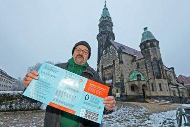 Der Zwickauer Grünen-Politiker Wolfgang Wetzel mit einem Flugblatt zurCovid-Impfung, dessen Inhalt er entschieden ablehnt.