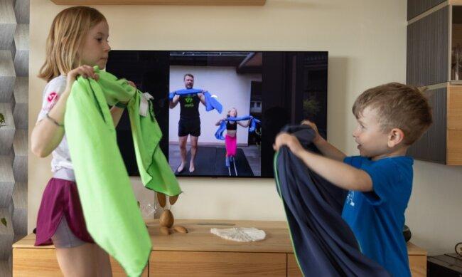Trainingseinheit mit dem Handtuch: Maxine (8 Jahre alt) und Hanno (5) aus Scheibenberg haben viel Spaß mit Ralf und Lotte Sommerfeldt - auch wenn's online ist. Nächsten Dienstag aber treffen sich die Kinder wieder zum Sport in Markersbach.