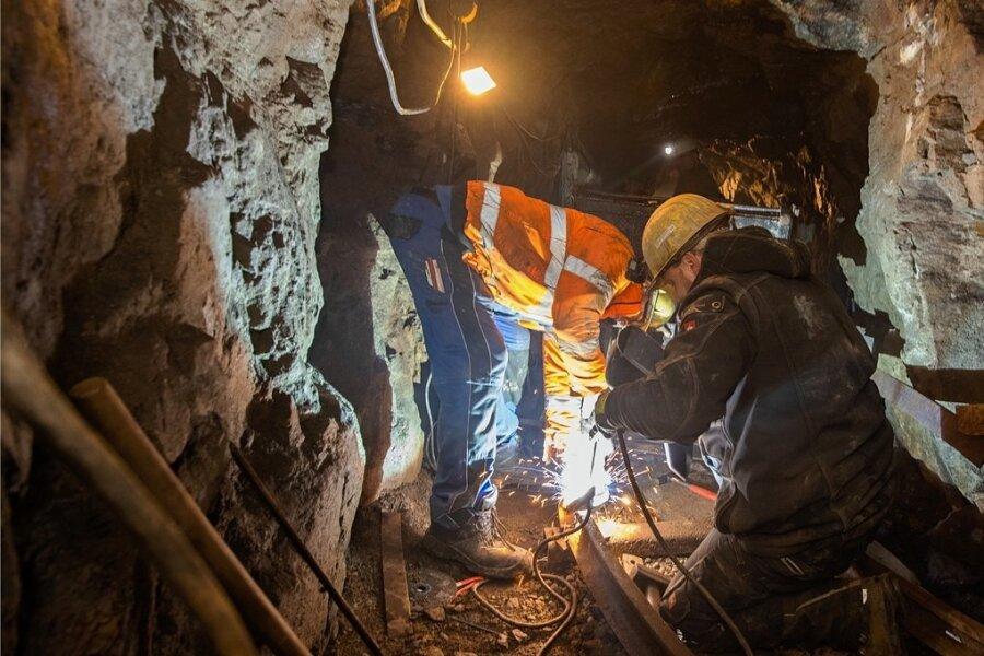 Arbeiten im Bergwerk war früher kein Zuckerschlecken und ist es heute auch nicht: Holger Piorek (links) und Kevin Schubert von der Bergsicherung Schneeberg verlegen derzeit das Felstreckengleis im Markus-Röhling-Stolln. Darüber sollen später die Sprengmassen abtransportiert werden.