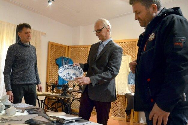 Konrad Kellner hält eine Schale mit einem Zwiebelmuster in der Hand. Das Motiv, eigentlich ein Granatapfel, kommt aus Asien. Mit im Bild: Detlev Köhler (links) und Sven Delitsch, alle sind von der Diakonie.