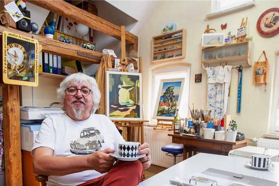 Alain Bonnas in seinem Taltitzer Atelier, das so voller Einfälle steckt, dass es unermüdlich zu erzählen scheint. Oben links im Foto der Kasten mit den Resten seines Weckers, den er am letzten Arbeitstag lustvoll mit dem Gabelstapler überfuhr. Es gibt hier auch satirische Skulpturen zum Coronavirus: Eine zeigt das Virus als Planeten, mit Klopapier und Nudeln als Trabanten.