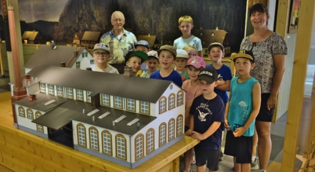 Mädchen und Jungen aus dem Mildenauer Hort stehen mit Claudia Schreiter und Lothar Schönherr am Modell der ehemaligen Pappenfabrik.