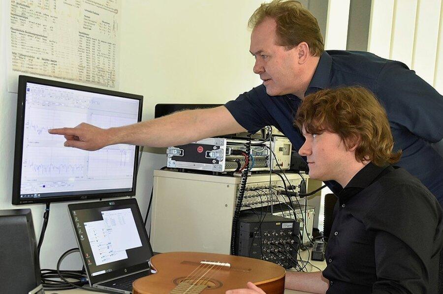 Schwingungsdetektive: Instituts-Geschäftsführer Holger Schiema (hinten) und Mitarbeiter Christoph Gilbert bei der Auswertung der Frequenzkurvenmessung an einer Konzertgitarre.