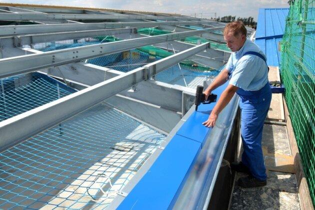 Wolfgang Wunderlich, Mitarbeiter der Firma Leuteritz Anlagenbau, befestigt gerade ein blaues Blech auf dem neuen Hallendach.