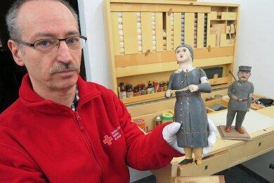 André Uebe, Leiter des Rot-Kreuz-Museums, zeigt die zwei Figuren, die er von einem Trödler bekam.