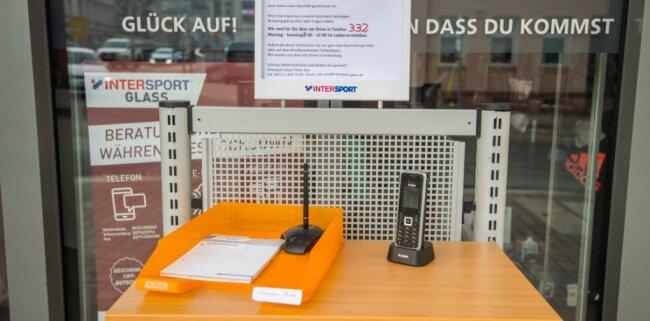 Einen Drive-In-Service bietet Intersport Glass in Aue an. Kontaktlos, weil per Kurzwahl durch die Glasscheibe der Eingangstür getrennt.