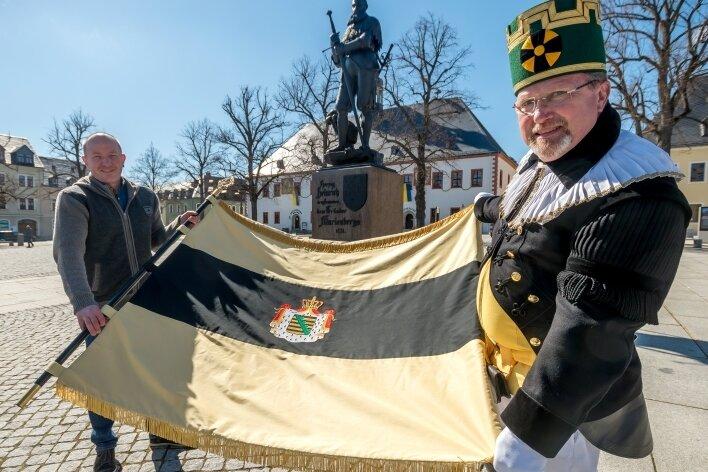 Schneidermeister Markus Seiler (l.) hat die von ihm gefertigte 1,5 mal 1,2 Meter große Fahne auf dem Markt offiziell an den Fahnensteiger der Marienberger Bergknappschaft, Ralf Albrecht, übergeben.