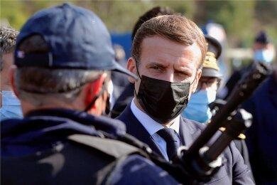 Frankreichs Staatschef Emmanuel spricht mit einem Vertreter der Polizei, die wegen Gewalttaten in der Kritik steht.