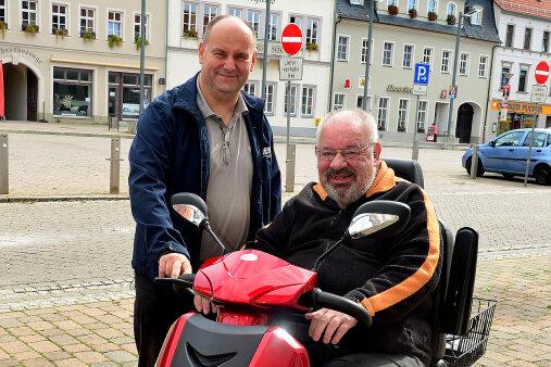 Uwe Sommerfeldt aus Frankenberg mit seinem neuen Rollstuhl-Fahrzeug, übergeben von Lutz Dick (l.) von Reha-aktiv aus Chemnitz.