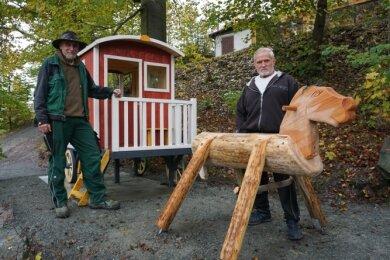Der Klingenthaler Tierparkchef Tino Richter (links) mit dem von ihm zusammengebauten Spielhaus und HorstEchtner, der das hölzerne Pferd geschaffen hat.