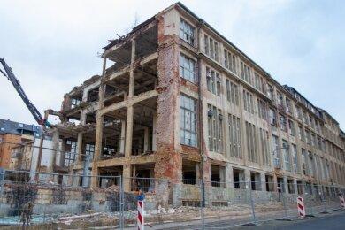 Der Arm des Abrissbaggers leistet ganze Arbeit: Stück für Stück wird das marode Industriegebäude jetzt abgetragen.