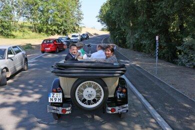 Bürgermeister Tino Obst, die CDU-Landtagsabgeordnete Kerstin Nicolaus und Landrat Christoph Scheurer auf dem Beifahrersitz fuhren das fertiggstellte Straßenstück in einem Oldtimer ab.