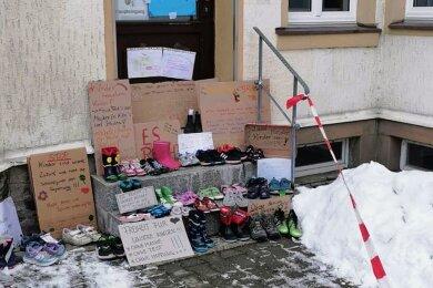 Mit Kinderschuhen und Plakaten vorm Rathaus machen unter anderem Eltern in Crottendorf auf ihre Situation und die der Kinder aufmerksam.