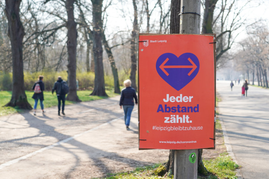 """Ein Plakat mit der Aufschrift """"Jeder Abstand zählt"""" der Stadt Leipzig hängt im Clara-Zetkin-Park. Zur Eindämmung der Ausbreitung des Coronavirus sind zahlreiche öffentliche Plätze gesperrt."""