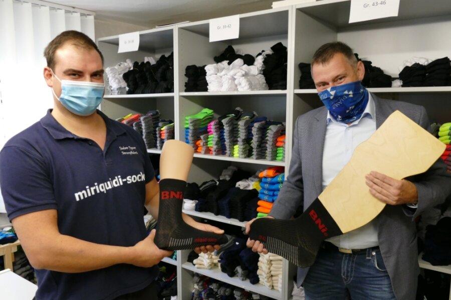 Stolz präsentieren Denny Sieber (links), der Geschäftsführer der Hopfgartener Strumpffabrik, und Jens Fiedler die neuen BNI-Socken. Die Buchstaben stehen für Business Network International - ein Unternehmernetzwerk, bei dem Fiedler als Regionaldirektor fungiert und das der Entwicklung von Siebers Firma helfen soll.