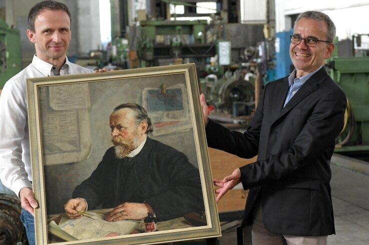 Geschäftsführer Uwe Maier nimmt das Geschenk von Ernst Reimar Paschke an die Pama entgegen: ein Gemälde von Firmengründer Ernst Ewald Paschke.