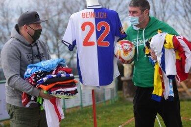 Abteilungsleiter Marcel Keßler (links) und Trainer Steffen Karl vom FSV Grün-Weiß Klaffenbach mit den zahlreichen Trikots, die der Verein aktuell für einen guten Zweck versteigert.