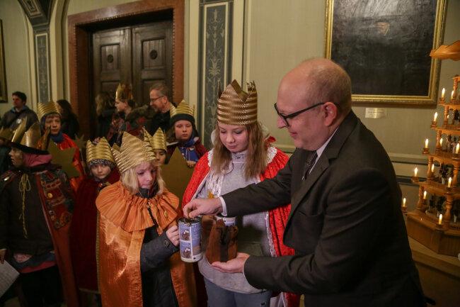 Bürgermeister Sven Schulze überreicht den Sternsingern eine Spende.
