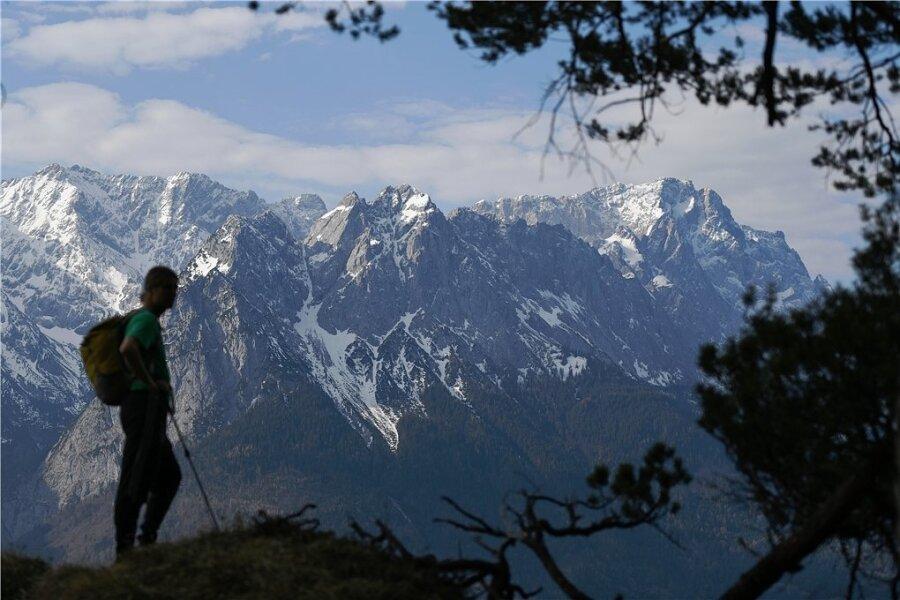 Ein Wanderer steht vor den schneebedeckten Gipfeln des Wettersteingebirges, rechts ist die Zugspitze zu sehen.