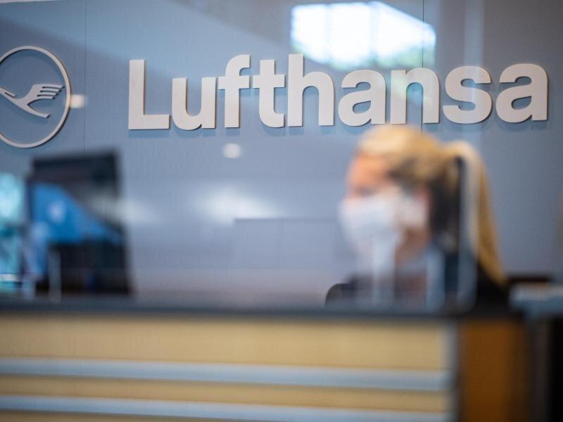 Eine Mitarbeiterin der Lufthansa sitzt mit ihrer Mund- und Nasenschutzmaske am Check-in im Flughafen Münster-Osnabrück.