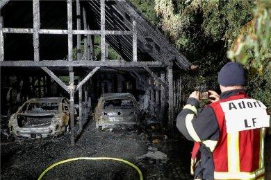 Ein Adorfer Feuerwehrmann fotografiert den ausgebrannten Doppelcarport an der Forststraße in Neukirchen. Brandursachenermittler waren am Freitag vor Ort. Die Polizei vermutet Brandstiftung.