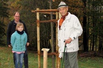"""Günter Kunzmann enthüllt gemeinsam mit Urenkelin Miriam sowie Toni Knorr das Schild an der """"Kunzmann-Eiche""""."""